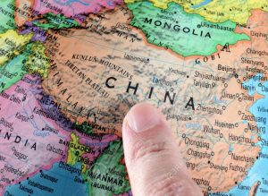 Finger pointing to China on a globe. Close-up.